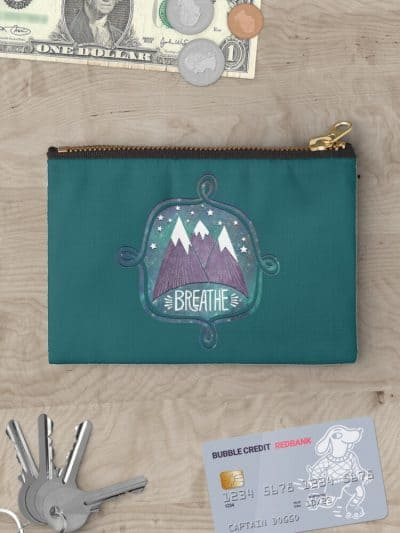 A Teal zipper pouch decorated with a small design of painted Purple Mountains surrounded by stars and the word breathe.,